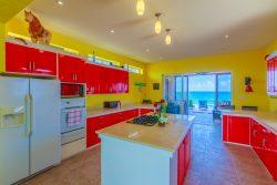 Gourmet kitchen looking into the indoor outdoor Caribbean room and infinity pool. Casa Música del Caribe